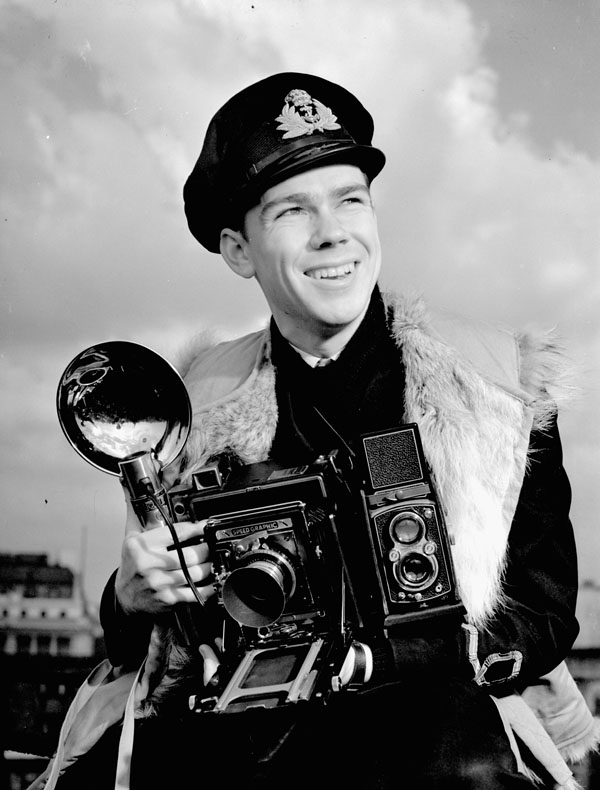Lieutenant John D. Mahoney of the Royal Canadian Navy Volunteer Reserve, holding an Anniversary Speed Graphic camera