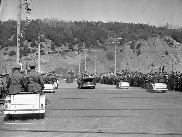 Royal Car, escorted by motorcycles and cars leaving Wolfe's Cove Dock to ascent Gilmour hill on way to Parliament Buildings. (item 1)