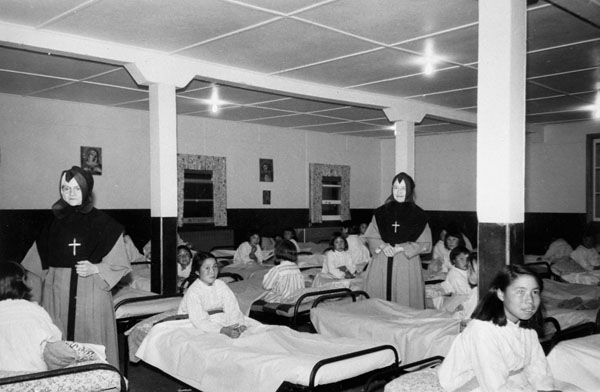 Turquetil Hall Residence (originally St. Mary's Residence), girls in their beds with two nuns, Chesterfield Inlet (Igluligaarjuk), September 5, 1958