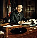Honourable Lester B. Pearson sitting at his desk.