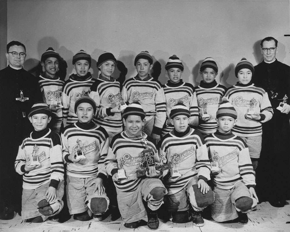 Maliotenam Indian Residential School, portrait of the hockey team and two priests, Quebec, ca. 1950