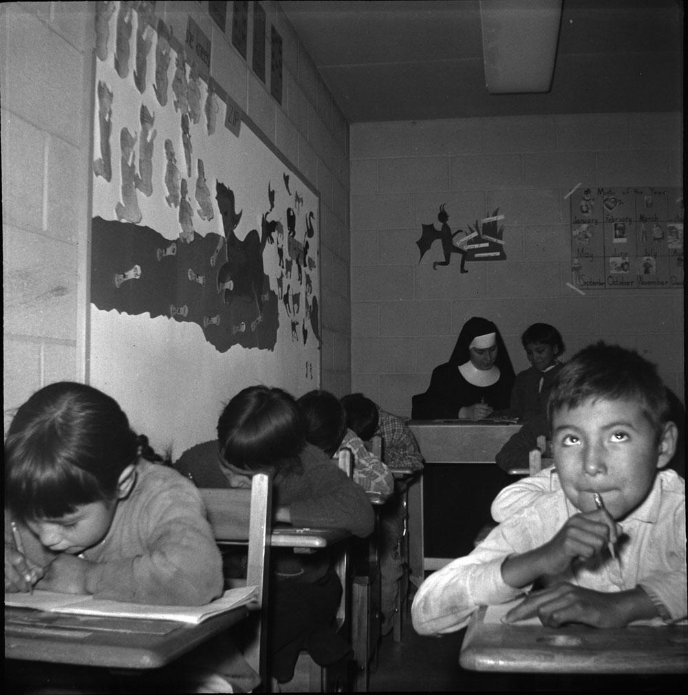 Pensionnat indien de Pukatawagan, jeune garçon avec d'autres élèves et une religieuse dans une salle de classe, vers 1960