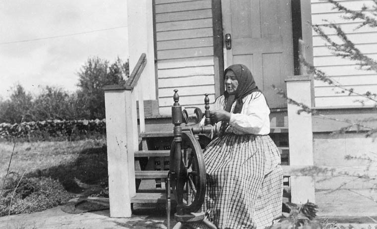 Malasha Cheveldayoff spinning at her farm at Blaine Lake, Saskatchewan. 1925. (item 1)