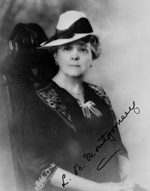 Black and white photograph of a woman sitting on a chair and wearing a hat and glasses