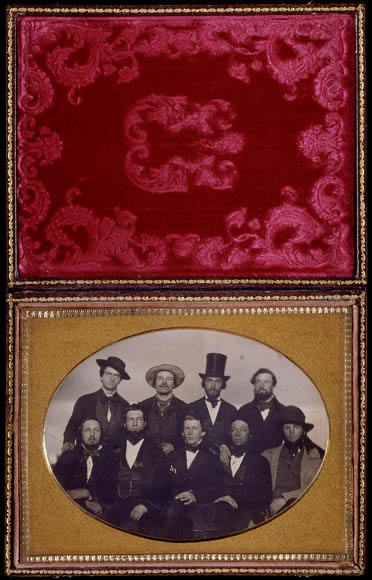 Image of a photo album showing the red cover and a photo of a group of men, the front row sitting and the back row standing.