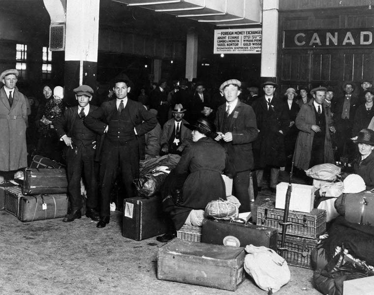 Black and white photograph of people standing amongst baggage at an immigration station