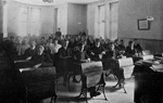 Black and white posed photograph of a large class of more than 30 students, seated at their desks and well dressed