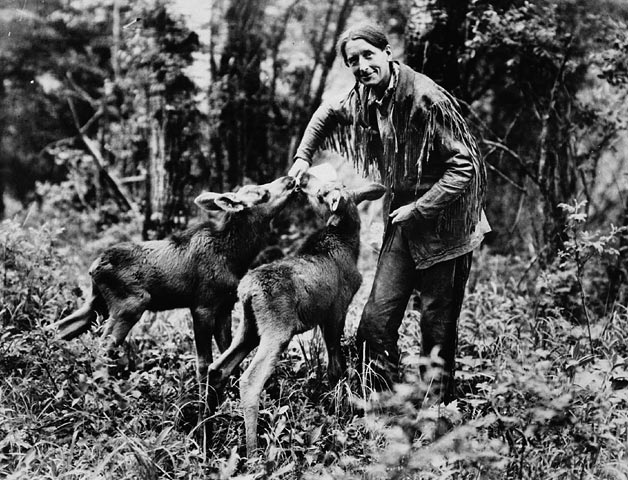 Photo of a man bottle-feeding two young moose.