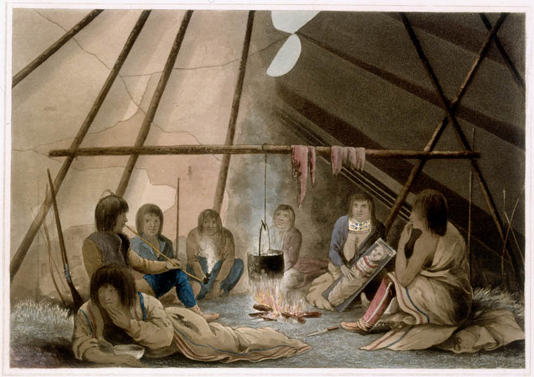 Image showing the inside of a tent with a group of people sitting around a fire. A woman is holding a baby.