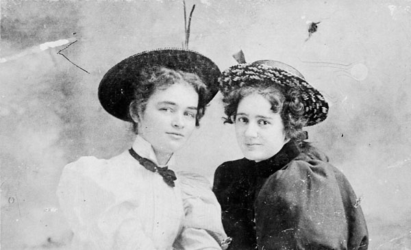 Black-and-white photo of two young women dressed in period costume