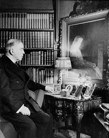 Rt. Hon. W.L. Mackenzie King sitting in front of the J.W.L. Forster painting of his mother, Isabel King, in the library at Laurier House