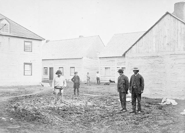 Black and white photograph of six men standing (three in the foreground, one in the middle ground and two in the background) in the vicinity of a group of four buildings.