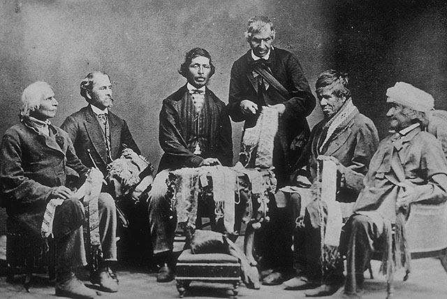 Black and white photograph of six men in suits, five seated and one standing in the middle. They are holding beaded belts and are gathered around a small table covered in beaded belts. The man seated on the far right is wearing a fur hat.