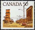 White 50-cent stamp with a colour illustration of a street lined with low-rise buildings, lampposts and a grain elevator