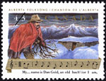 White 43-cent stamp with a colour illustration of a man carrying kindling, a snow-covered cabin and mountains in the background, and music notes and lyrics at the bottom