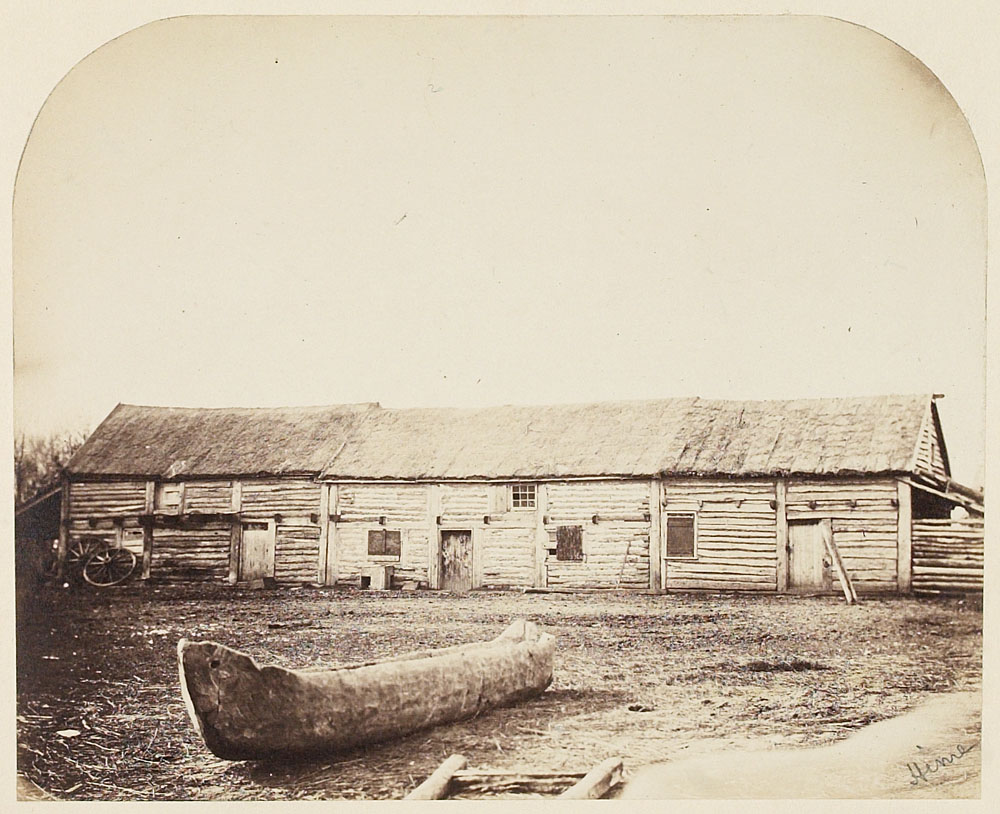 Black and white photograph of a wooden canoe on the ground in front of a long wooden building with a thatched roof.