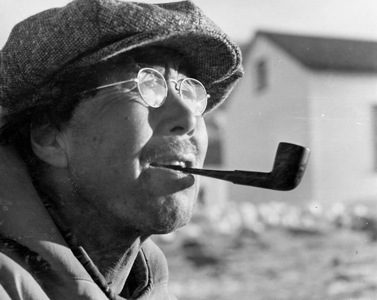 Photographie en noir et blanc du profil d'un homme inuit portant des lunettes et une casquette en laine et fumant la pipe, Qikiqtat (Kekerten), baie Cumberland, Nunavut, date inconnue
