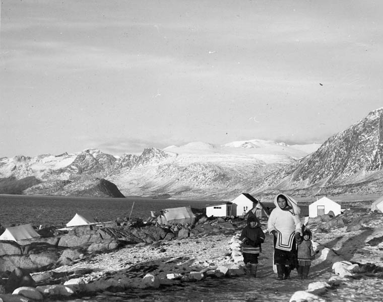 Inuit woman and children. Buildings in the background were formerly used by the Hudson's Bay Company as a whale-oil plant.