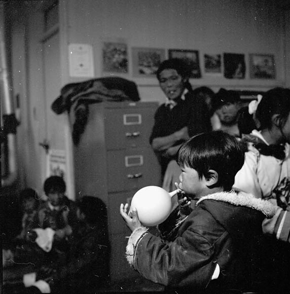 Cape Dorset (Kinngait) Federal Hostel, a  boy blowing up a balloon during a dance held in the school, August 1961