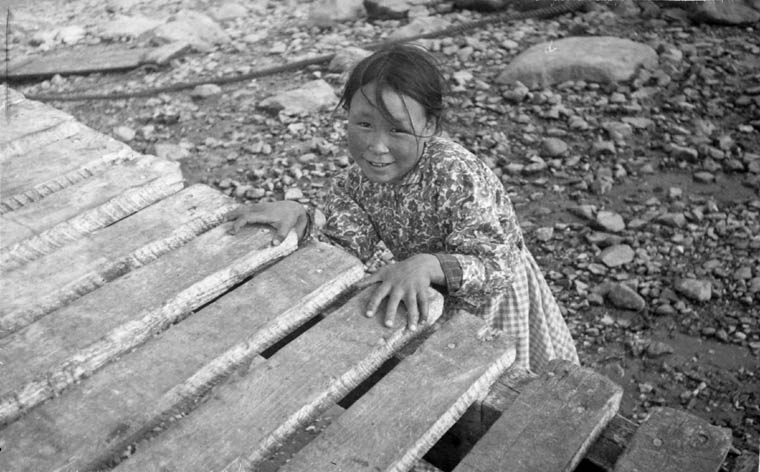 Black-and-white photograph of an Inuit girl standing behind a wooden platform smiling into the camera, probably Coral Harbour, Southampton Island, Nunavut, ca. 1945–46