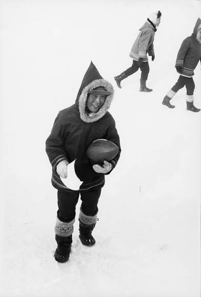 Cape Dorset (Kinngait) Federal Hostel, boy in the snow holding a football with two other boys in the background during recess, April 1964