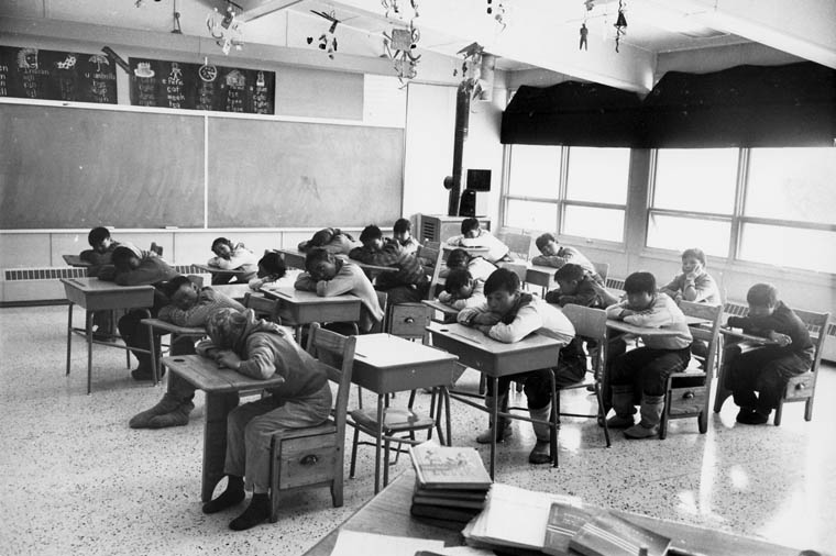 Cape Dorset (Kinngait) Federal Hostel, students seated in a classroom resting their heads on their desks, April 1964