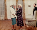 Colour photograph of two women shaking hands, standing beside an armchair in a large formal room