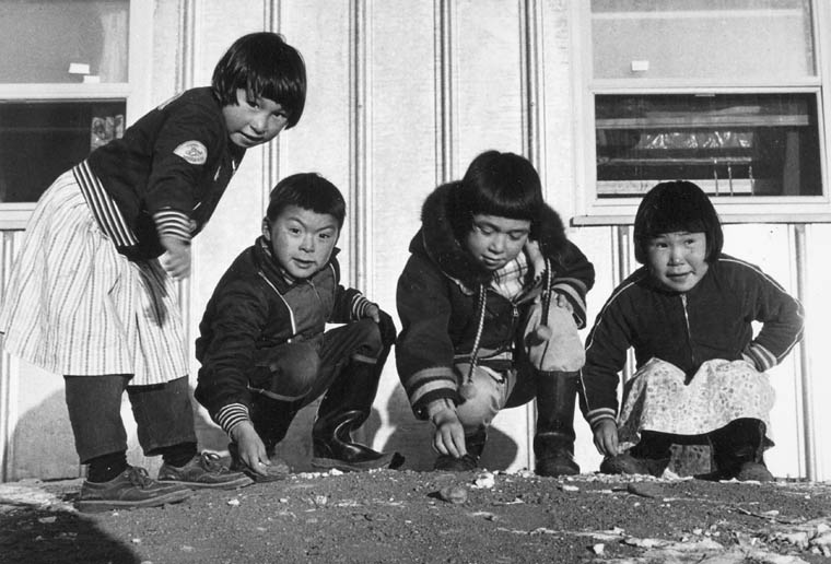 Four Inuit children playing in front of a building. (item 1)
