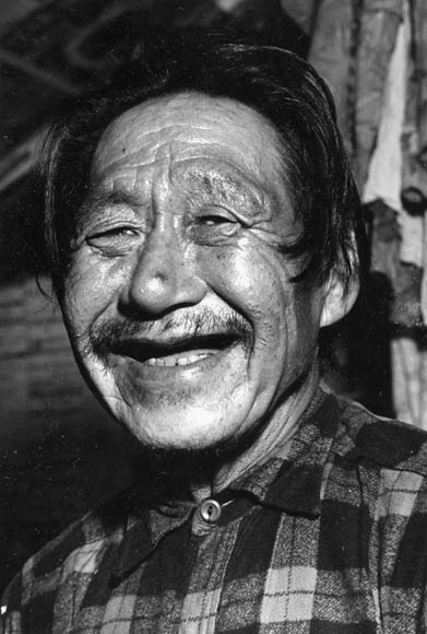 Portrait of an unidentified Inuit male wearing a plaid shirt. (item 1)