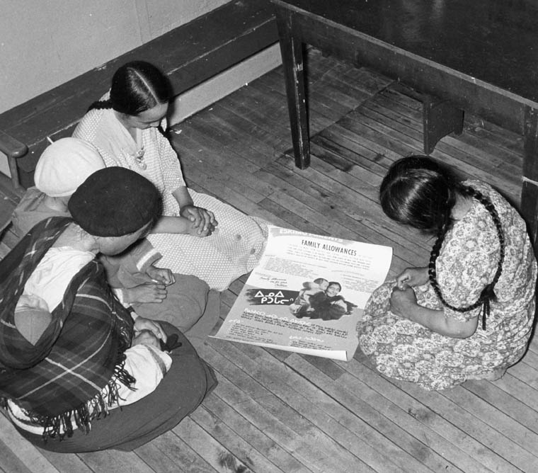 Women looking at a family allowance poster, Baker Lake (Qamanittuaq), Nunavut, by unknown photographer, Health and Welfare Canada.