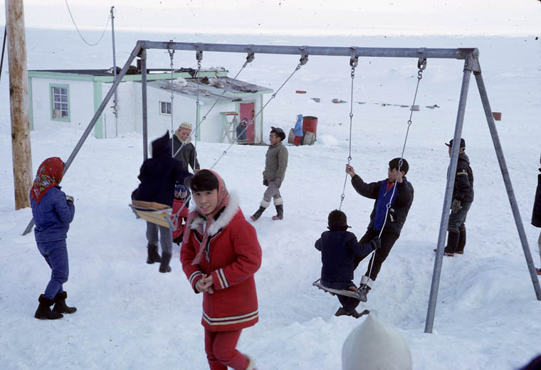 Igloolik (Iglulik) Federal Hostel, student, Elizabeth Aapak Rose, standing in the foreground with a group of children playing on swings in the snow, May 1965