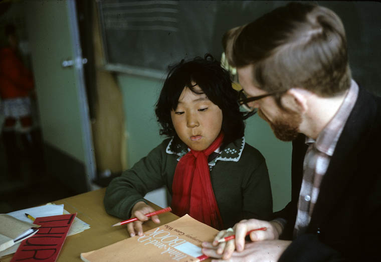 Igloolik (Iglulik) Federal Hostel, girl at her desk receiving instructions from her teacher, May 1965