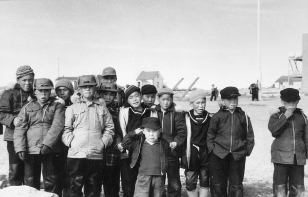 Sir Joseph Bernier Federal Day School (Turquetil Hall), group of male students standing in the school playground, Chesterfield Inlet (Igluligaarjuk), September 5, 1958