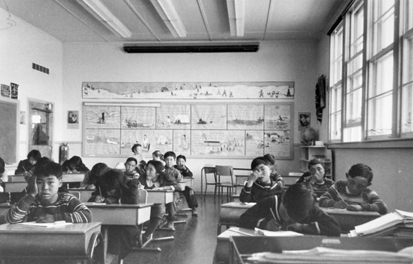 Sir Joseph Bernier Federal Day School (Turquetil Hall), group of students working at their desks in a classroom. Rene Otak is on far left, Chesterfield Inlet (Igluligaarjuk), September 5, 1958