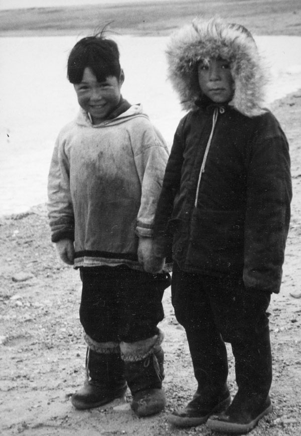 Two boys, Kutik (Richard Immaroitok) on the left and Louis Tapadjuk on the right, standing onshore just before their departure to federal day school, Igloolik (Iglulik), September 12, 1958