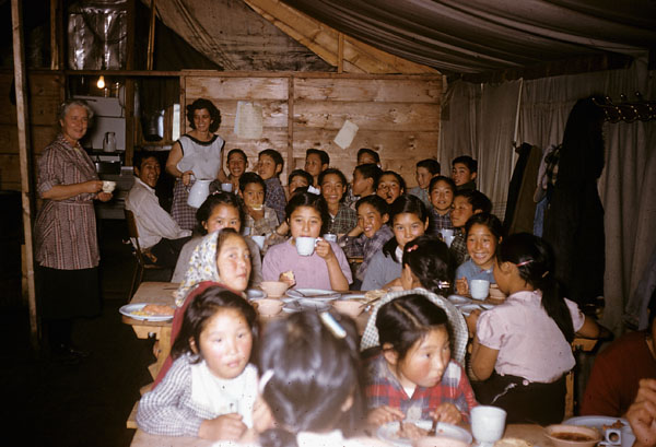 Coppermine (Kugluktuk) school (Tent Hostel), group of students eating in the dining tent with school personnel [1958]