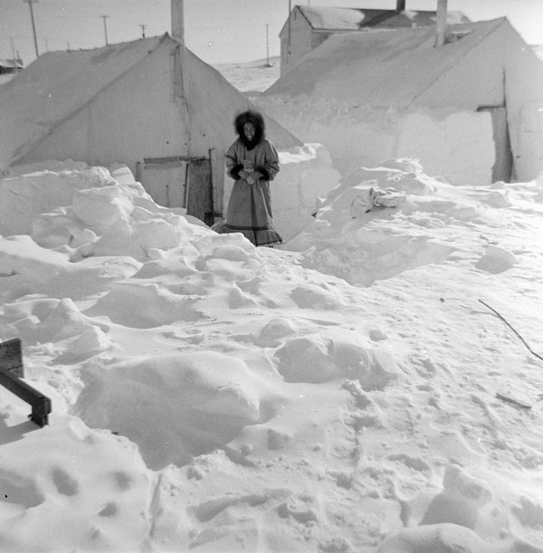 Coppermine (Kugluktuk) school (Tent Hostel), Inuit woman standing in the snow in front of a tent entrance, 1959