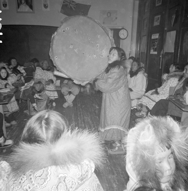 Coppermine (Kugluktuk) school (Tent Hostel), Inuit woman, Maria, doing a drum dance in front of a group of students and adults in a classroom, 1959