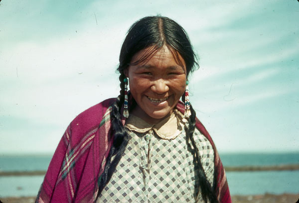 Colour photograph of an Inuit woman smiling and standing outside with a coastline in the background, Arviat, Nunavut, ca. 1930s