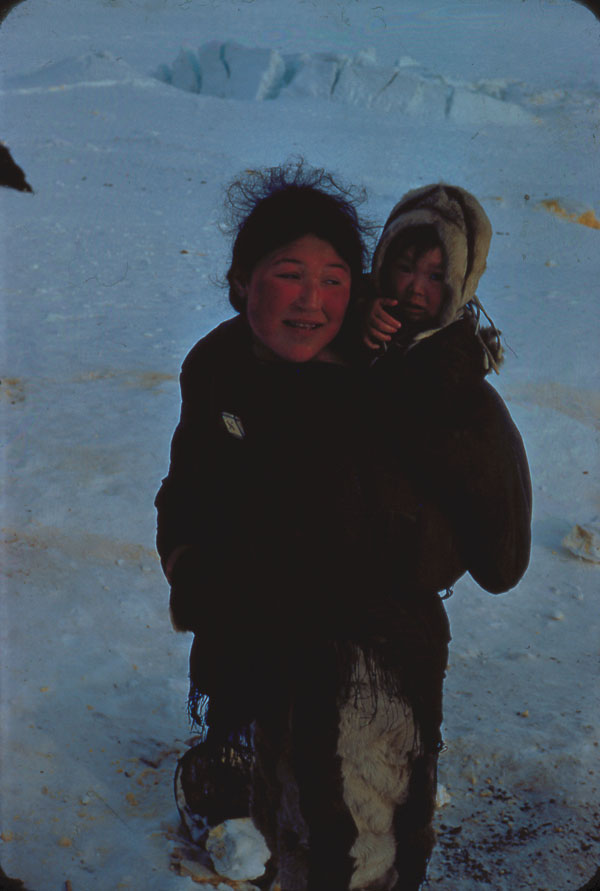 Inuit mother with child in hood of amautik. (item 1)