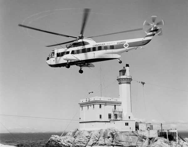 Photo of a Canadian Coast Guard helicopter in front of the Triple Island light station, Prince Rupert, British Columbia, in July 1967.