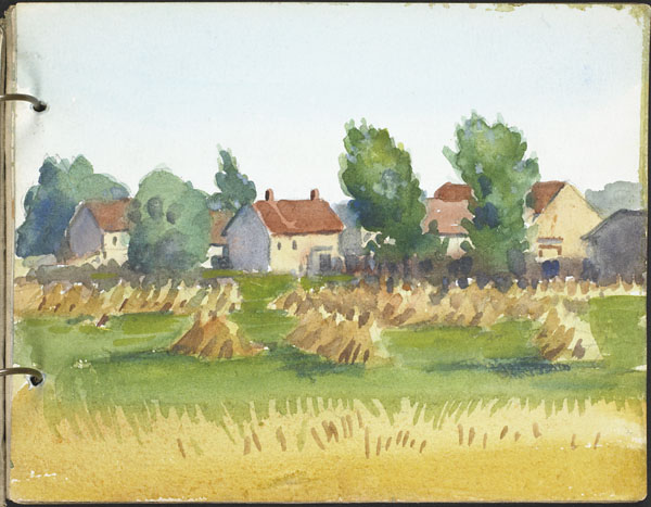 View of a town bordered by fields of haystacks