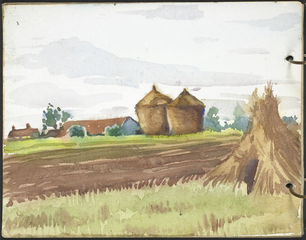 View of a field with large haystacks and red-roofed buildings