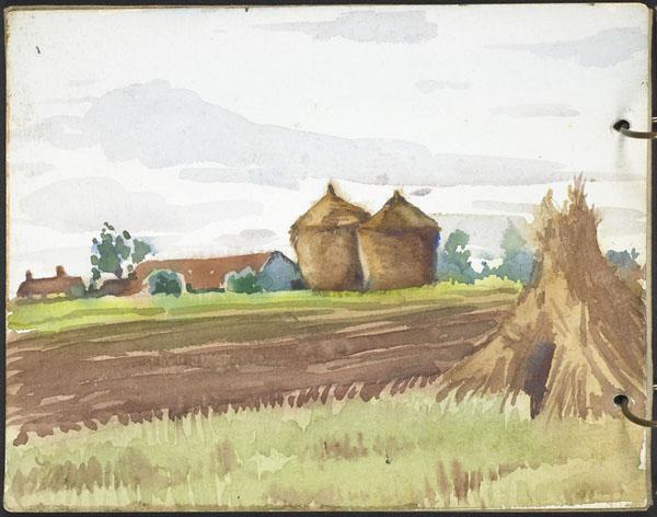 Vue d'un champ avec de grandes meules de foin et des bâtiments aux toits rouges
