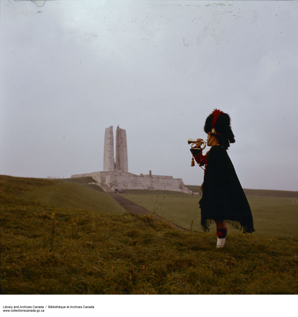 Photograph of Vimy Memorial with  a man in Highland dress playing a bugle in foreground