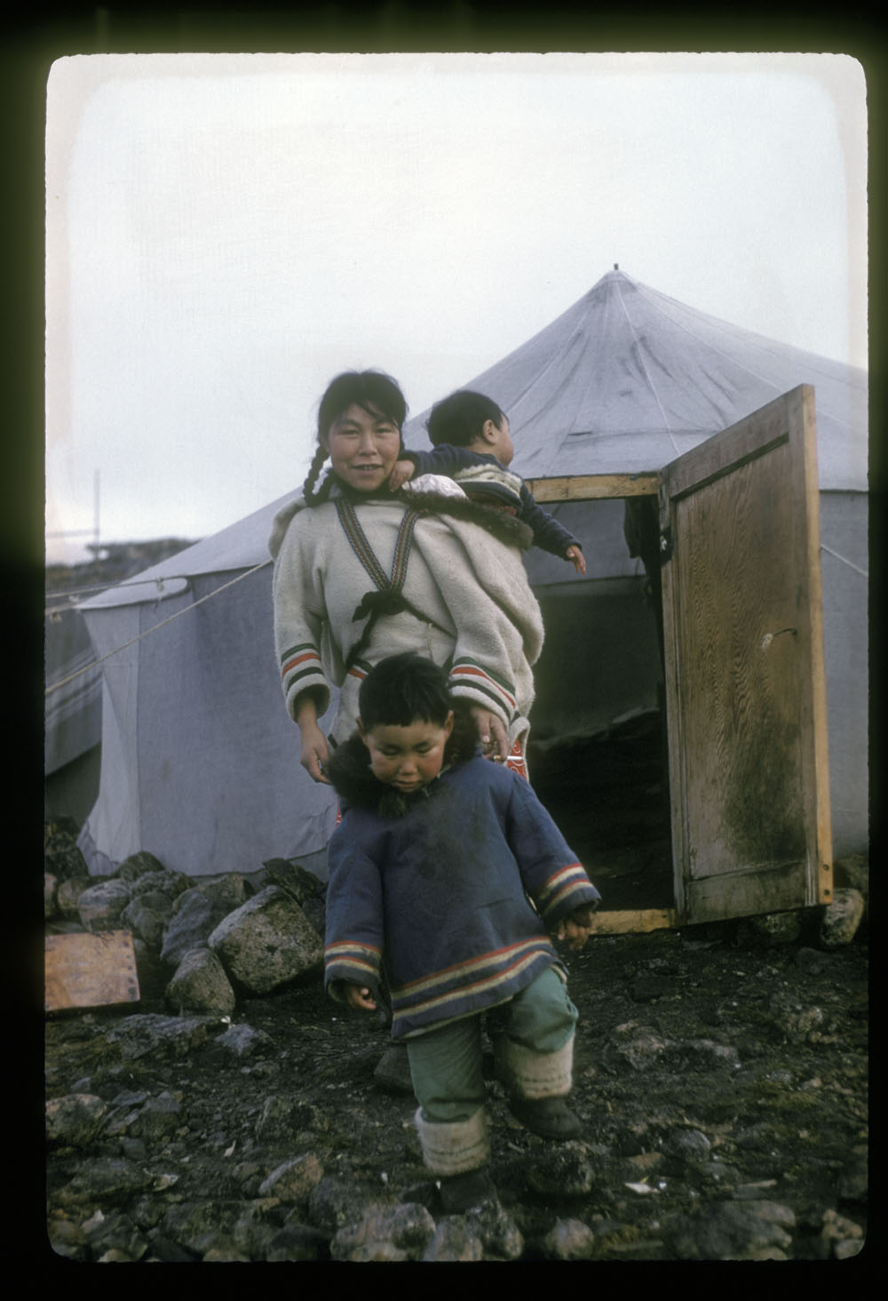 an Inuit woman standing with her son in front of a canvas tent carrying a baby in the hood of her parka, Kinngait, Nunavut, late summer 1960