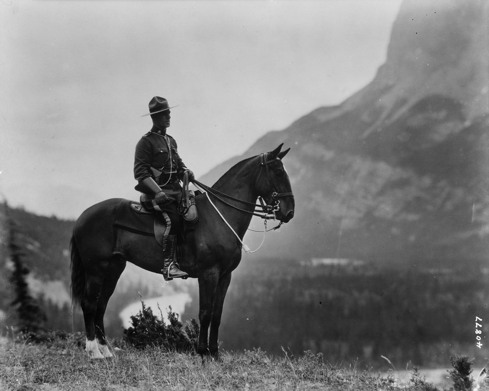 Black-and-white image of an officer in uniform sporting a western-style Stetson, seated on a horse, with the Canadian Rockies in the background.