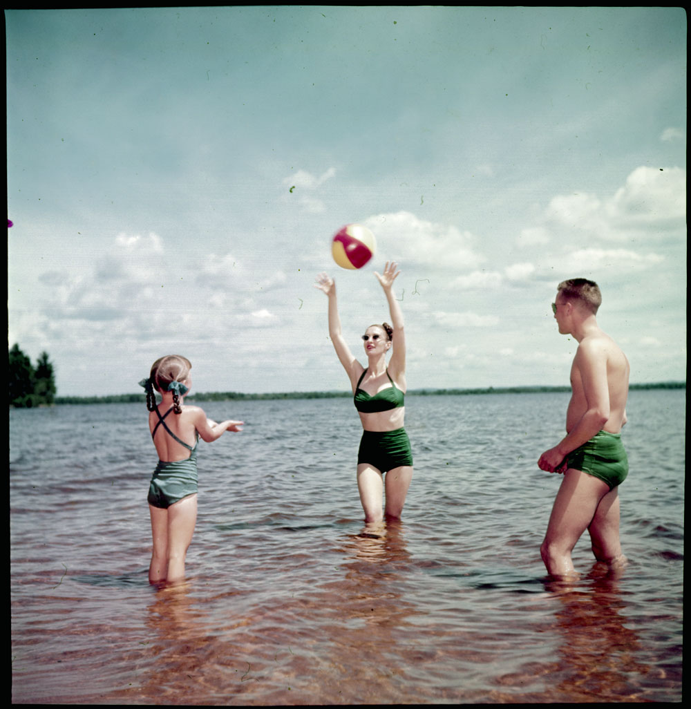Photo of a woman, a man and a young girl playing with a beach ball in the lake.