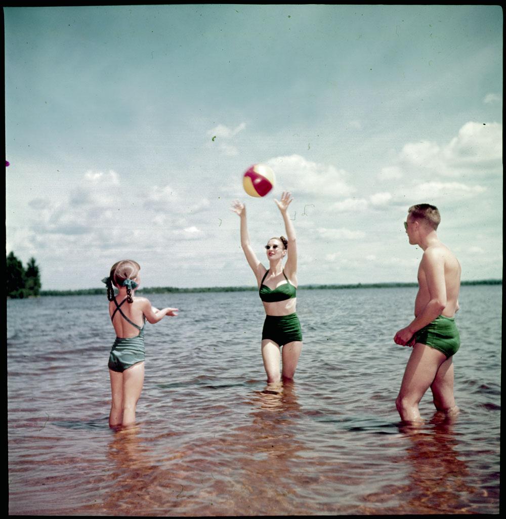 Photo d'une femme, un homme et une jeune fille jouant avec un ballon de plage dans un lac.