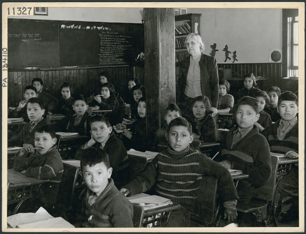All Saints Indian Residential School, Cree students at their desks with their teacher in a classroom, Lac La Ronge, March 1945